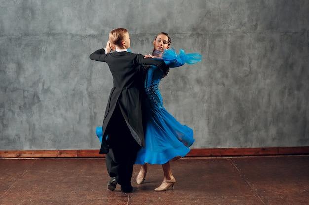 Młody mężczyzna i kobieta tańczą walca w sali balowej