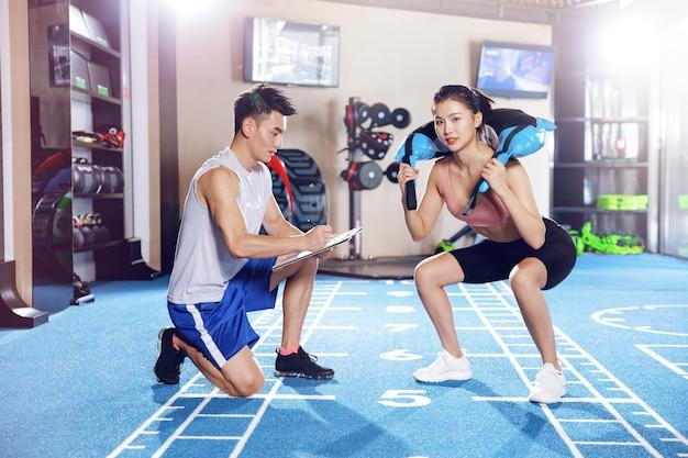 Młody mężczyzna i kobieta, trening w siłowni