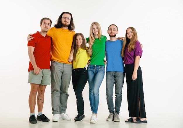 Młody mężczyzna i kobieta ubrani w kolory flagi lgbt na białym tle. kaukaskie modele w jasnych koszulach.