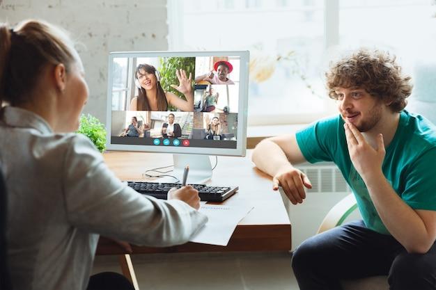 Młody mężczyzna i kobieta uczestniczą w wideokonferencji patrząc na ekran laptopa podczas wirtualnego spotkania, aplikacja kamery wideorozmowy dla biznesu, z bliska. praca zdalna, freelance, edukacja, koncepcja stylu życia.