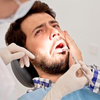 Młody mężczyzna i kobieta w badaniu stomatologicznym u dentysty