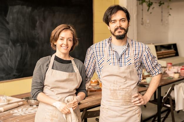 Młody mężczyzna i kobieta w fartuchach stojąc w miejscu pracy podczas wspólnej pracy