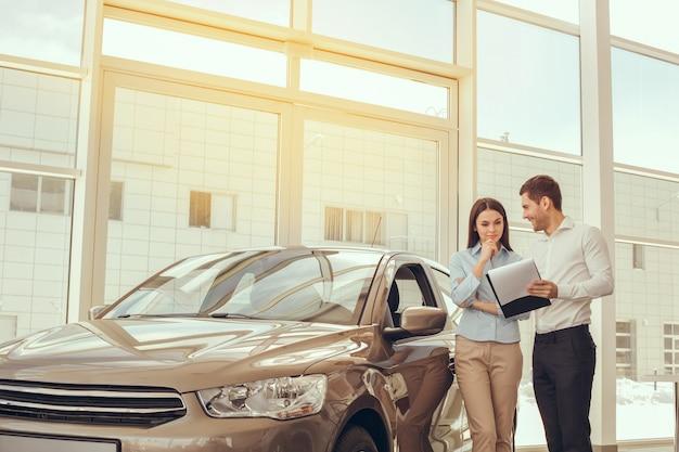 Młody mężczyzna i kobieta w podpisaniu umowy na wynajem samochodu car