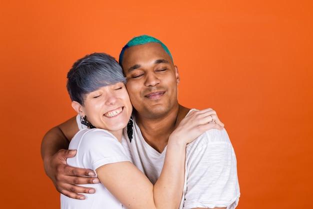 Młody mężczyzna i kobieta w swobodnej bieli na pomarańczowej ścianie przytulają się mocno, trzymając się mocno