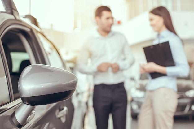 Młody mężczyzna i kobieta w umowie o wynajem samochodu