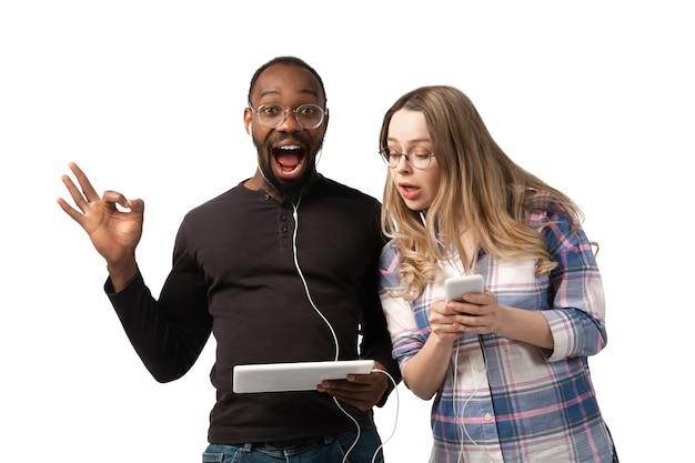 Młody mężczyzna i kobieta za pomocą laptopa, urządzeń, gadżetów na białym tle na białej ścianie. koncepcja nowoczesnych technologii, tech, emocje, reklama. miejsce. zakupy, gry, spotkania online edukacja.