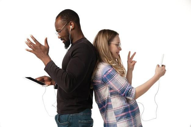 Młody mężczyzna i kobieta za pomocą laptopa, urządzeń, gadżetów na białym tle na białej ścianie. koncepcja nowoczesnych technologii, tech, emocje, reklama. miejsce. zakupy, gry, spotkanie z edukacją online.