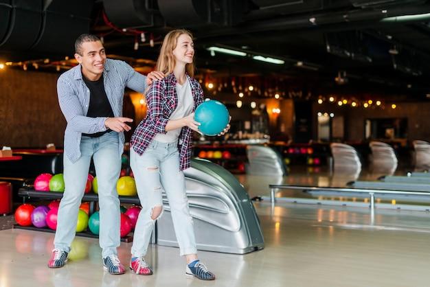 Młody mężczyzna i kobieta zabawy w kręgielni