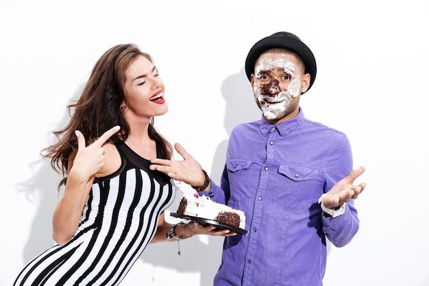Młody mężczyzna i ładna dziewczyna żartują na białym tle