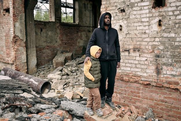 Młody mężczyzna i mała dziewczynka stoją przy zrujnowanym budynku