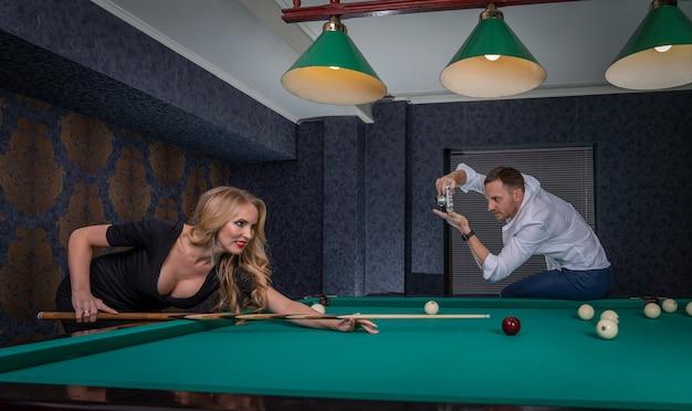 Młody mężczyzna i seksowna kobieta mają sesję zdjęciową w sali bilardowej