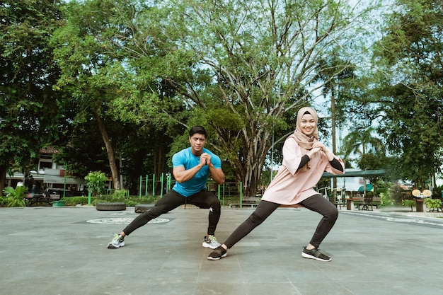 Młody mężczyzna i zawoalowana dziewczyna w strojach gimnastycznych wykonują razem ruch rozgrzewki nóg przed ćwiczeniami w parku