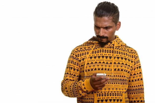 Młody mężczyzna indyjski trzymając telefon komórkowy podczas myślenia