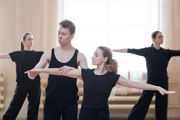 Młody mężczyzna instruktor tańca pomaga jednej z kobiet z wyciągniętymi rękami podczas treningu w nowoczesnym studio