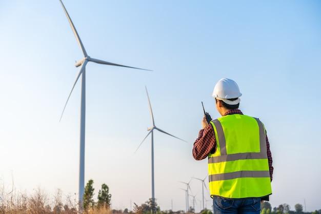 Młody mężczyzna inżynier używa walkie talkie do sprawdzania systemu przed farmą turbin wiatrowych