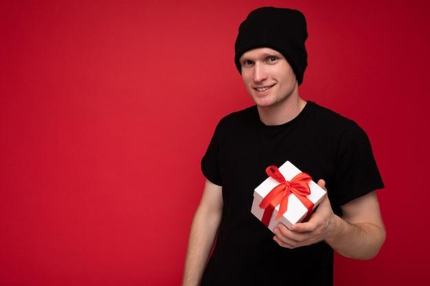 Młody mężczyzna izolowanych na czerwonym tle ściana ma na sobie czarny kapelusz i czarną koszulkę, trzymając białe pudełko z czerwoną wstążką i patrząc na kamery. skopiuj miejsce, makieta