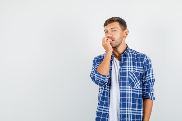 Młody mężczyzna jedzący paznokcie w koszuli i patrząc skupiony. przedni widok.