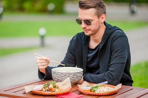 Młody mężczyzna jedzenie zabrać makaron na ulicy