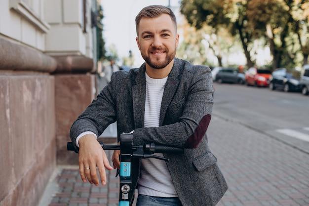 Młody mężczyzna jedzie na skuterze elektrycznym w mieście