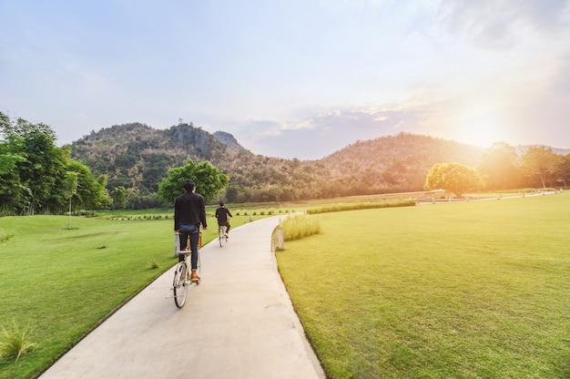 Młody mężczyzna jedzie retro rowerem w publicznym parku ze światłem słonecznym