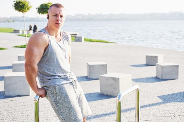 Młody mężczyzna jogger sportowiec, trening i trening na świeżym powietrzu w mieście.