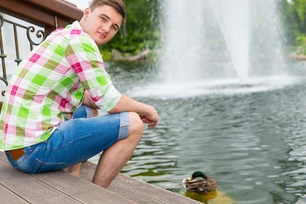 Młody mężczyzna karmi kaczki w stawie, siedząc na drewnianym pokładzie w parku z fontanną w tle
