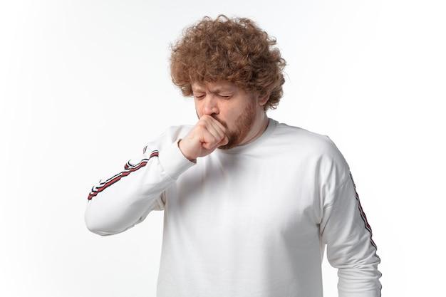 Młody mężczyzna kaszle na białej ścianie