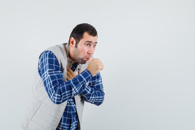 Młody mężczyzna kaszle w koszuli, kurtce bez rękawów i wygląda na chorego, widok z przodu. miejsce na tekst