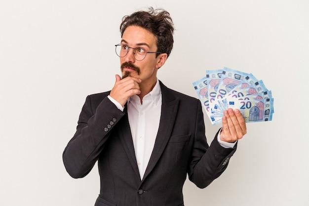 Młody mężczyzna kaukaski gospodarstwa banknotów na białym tle patrząc w bok z wyrazem wątpliwym i sceptycznym.