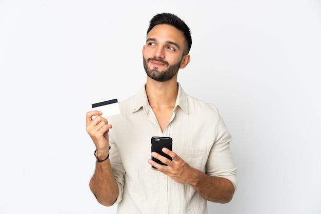 Młody mężczyzna kaukaski na białym tle kupowanie za pomocą telefonu komórkowego przy użyciu karty kredytowej podczas myślenia