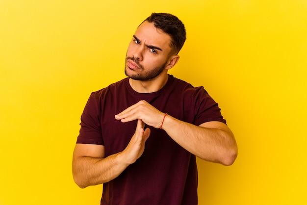 Młody mężczyzna kaukaski na białym tle na żółtym tle pokazując gest limitu czasu.