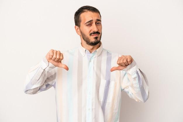 Młody mężczyzna kaukaski na białym tle pokazując kciuk w dół, koncepcja rozczarowanie.