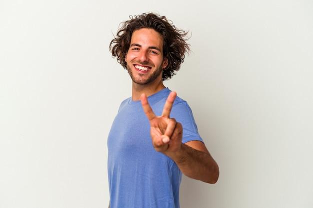 Młody mężczyzna kaukaski na białym tle pokazując znak zwycięstwa i uśmiechając się szeroko.