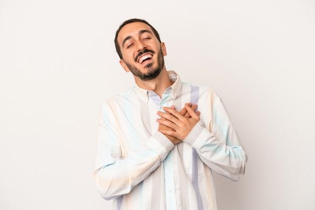 Młody mężczyzna kaukaski na białym tle śmiejąc się trzymając ręce na sercu, pojęcie szczęścia.