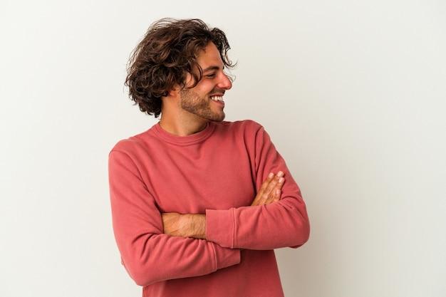 Młody mężczyzna kaukaski na białym tle uśmiechający się pewnie ze skrzyżowanymi rękami.