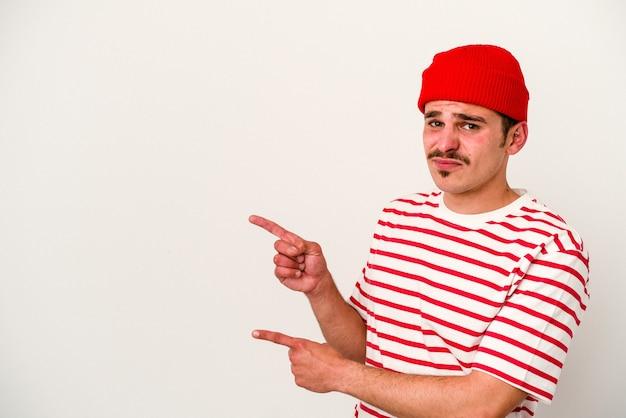 Młody mężczyzna kaukaski na białym tle w szoku, wskazując palcami wskazującymi na miejsce.