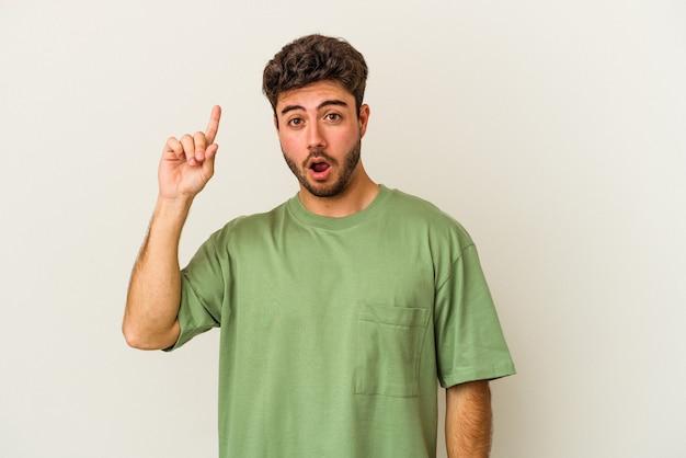 Młody mężczyzna kaukaski na białym tle wskazując do góry z otwartymi ustami.