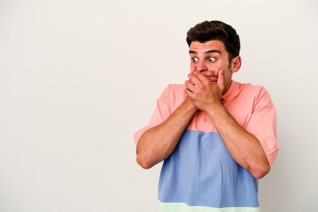 Młody mężczyzna kaukaski na białym tle zamyślony patrząc na miejsce obejmujące usta ręką.