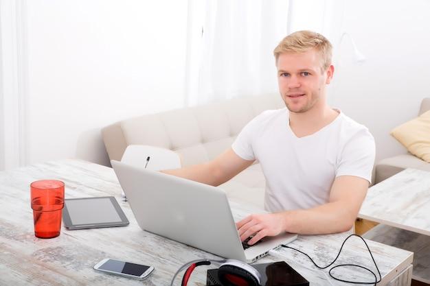 Młody mężczyzna kaukaski pracujący w swoim domowym biurze.