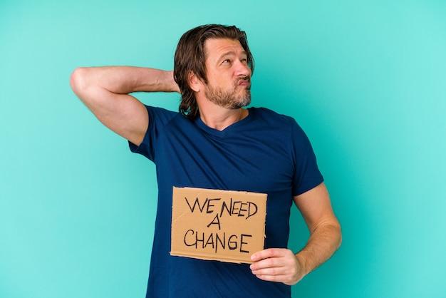 Młody mężczyzna kaukaski średnim wieku gospodarstwa potrzebujemy tabliczki zmiany samodzielnie na niebieskiej ścianie