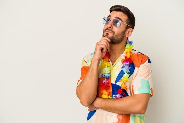 Młody mężczyzna kaukaski taniec na imprezie hawajskiej na białym tle, patrząc w bok z wyrazem wątpliwości i sceptyczny.
