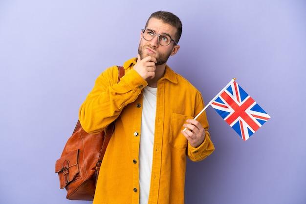 Młody mężczyzna kaukaski trzymając flagę zjednoczonego królestwa na białym tle na fioletowy, mając wątpliwości