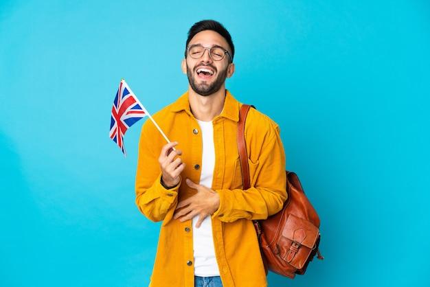 Młody mężczyzna kaukaski trzymając flagę zjednoczonego królestwa na białym tle na żółtym tle dużo uśmiecha się