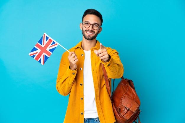 Młody mężczyzna kaukaski trzymając flagę zjednoczonego królestwa na białym tle na żółtym tle zaskoczony i wskazując przód