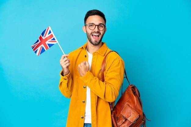 Młody mężczyzna kaukaski trzymając flagę zjednoczonego królestwa na białym tle