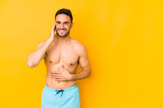 Młody mężczyzna kaukaski z kostium kąpielowy samodzielnie na żółtym tle młody mężczyzna kaukaski z trlaughs szczęśliwie i ma zabawy trzymając ręce na brzuchu.