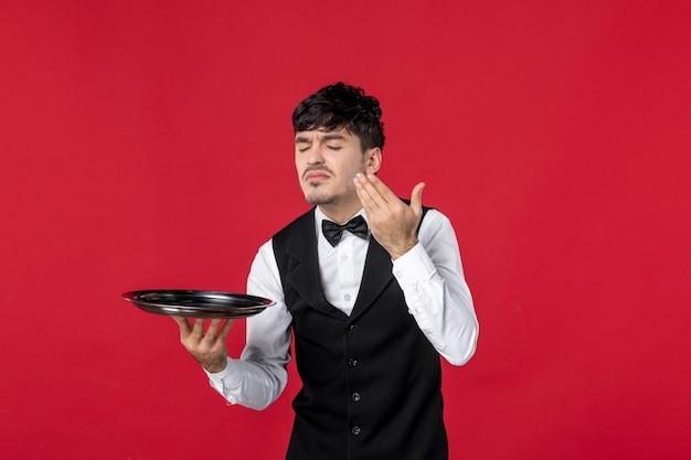 Młody mężczyzna kelner w mundurze wiązany motyl na szyi trzymający tacę pachnącą na pojedynczym czerwonym tle