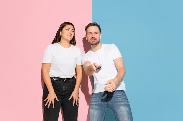 Młody mężczyzna, kobieta dorywczo na różowym, niebieskim, dwukolorowym tle.
