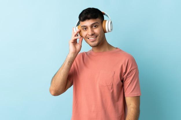 Młody mężczyzna kolumbijczyk na niebieskim tle słuchania muzyki