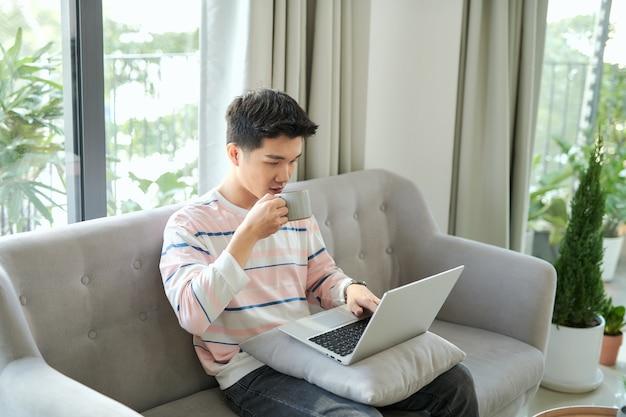 Młody mężczyzna korzysta z laptopa w domu